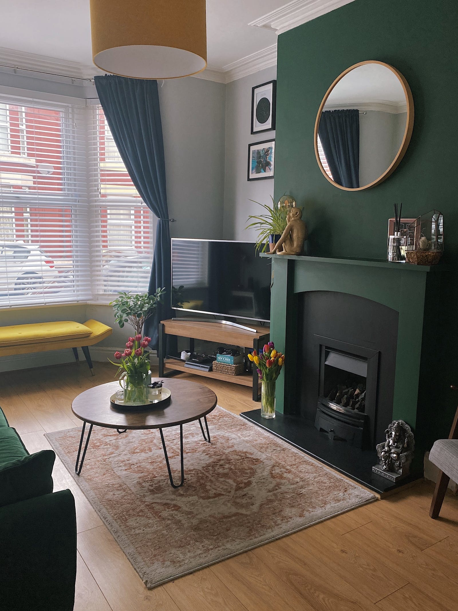 Living room with a statement wall and fireplace painted in dark green colour