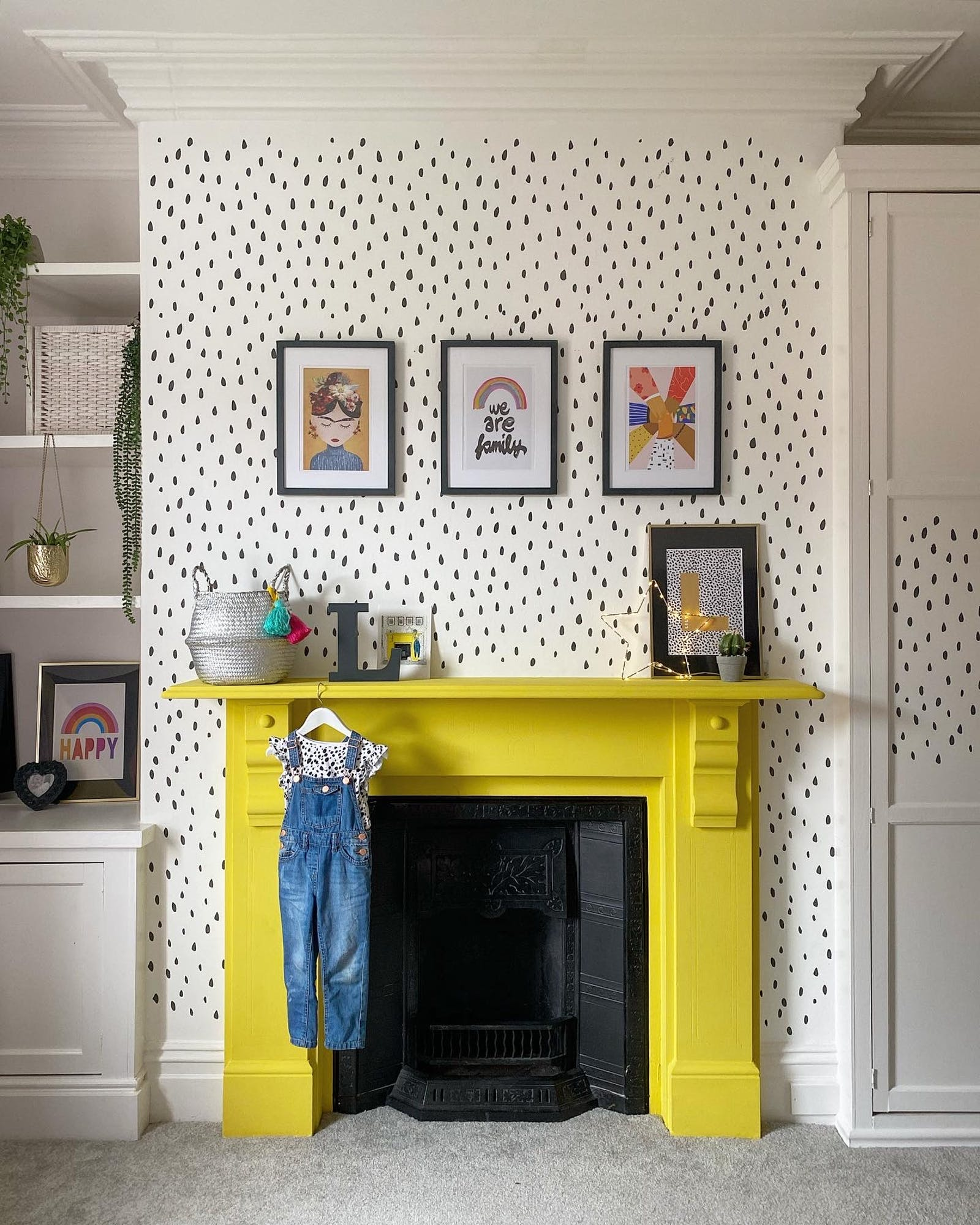 Patterned wall with wall art and a fireplace painted in yellow