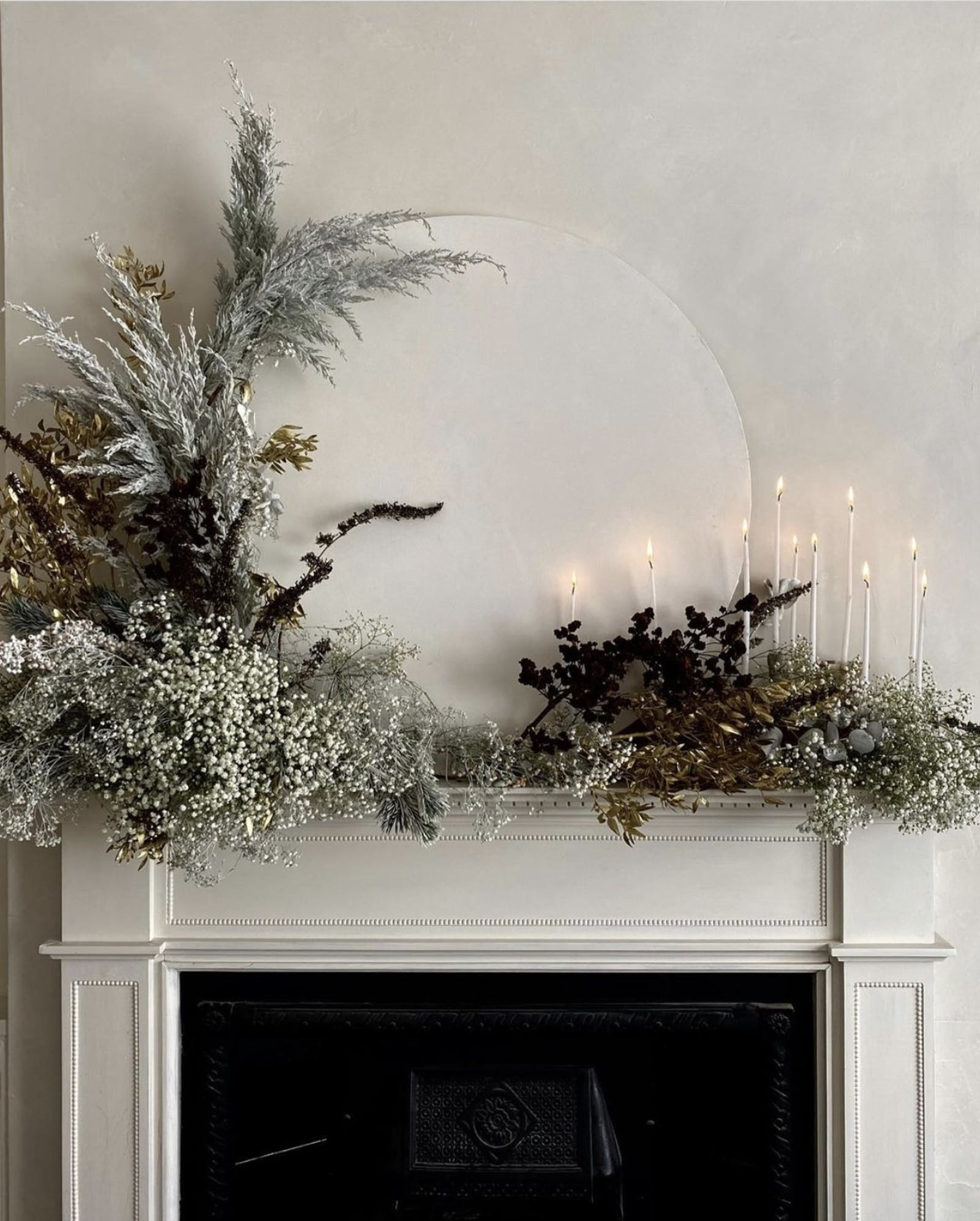 Foliage mantle display on fireplace with candles