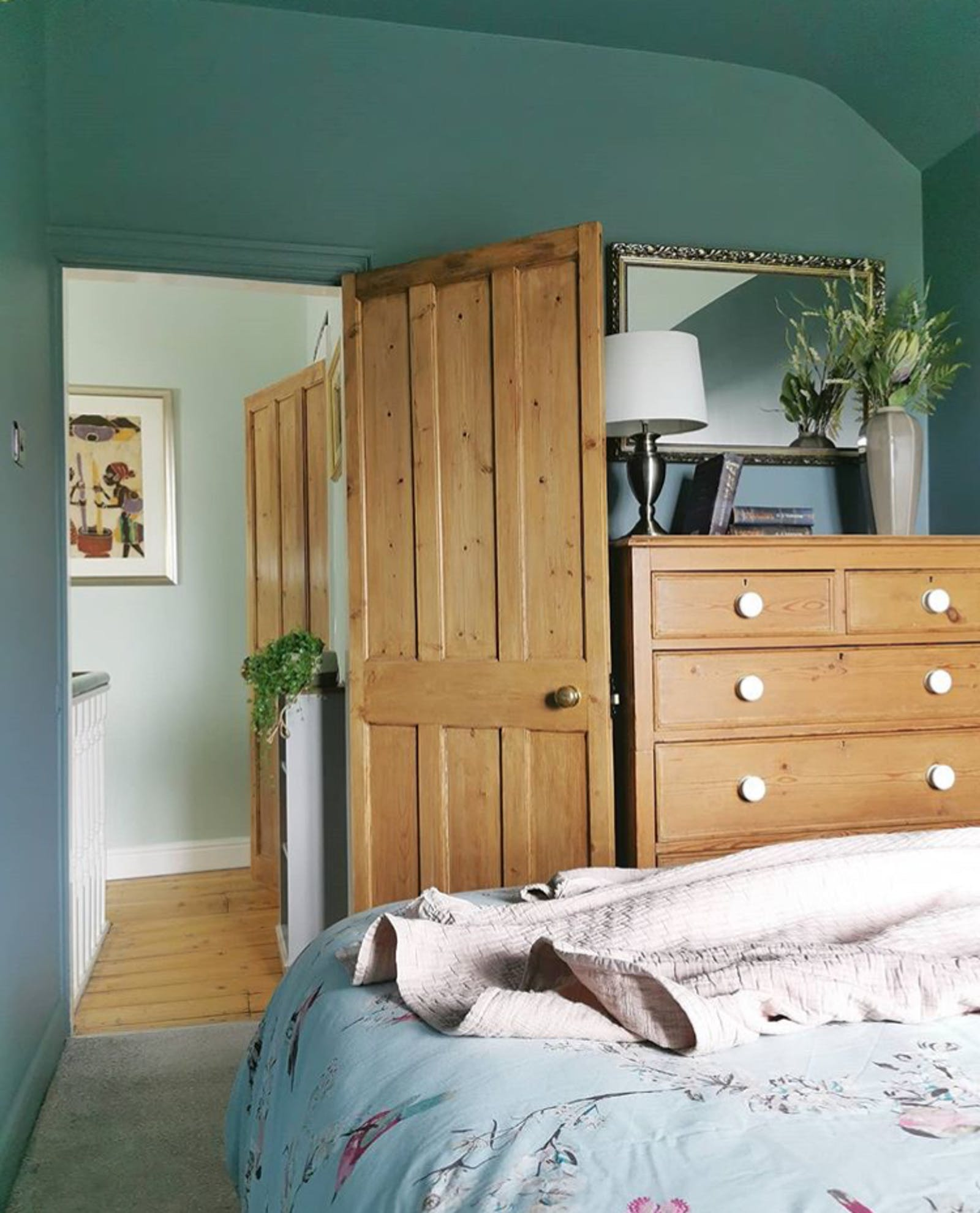 Bedroom wall painted in Lick Teal 03 with wooden furnishings