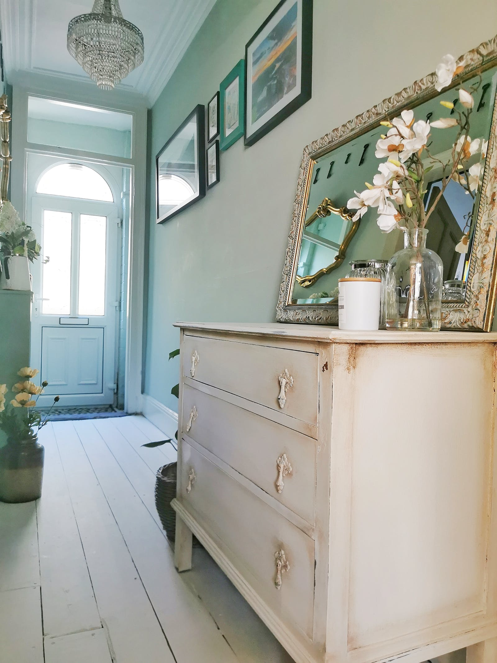 A massive vintage chest of drawers painted in white, placed in a light green hallway with framed pictures on the walls