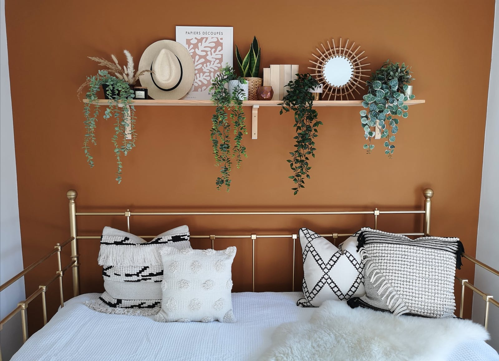 Room featuring Orange 02 feature wall, sofa with bohemian cushions and hanging plants