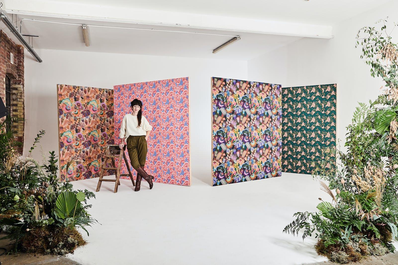 Artist Natasha Coverdale standing in front of 4 Lick x Natasha Coverdale wallpaper designs