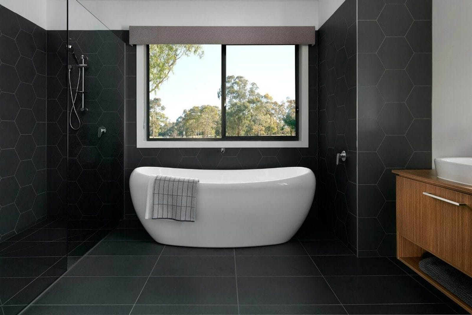 Black bathroom with big black tiles and a bathtub, placed in front of a big window