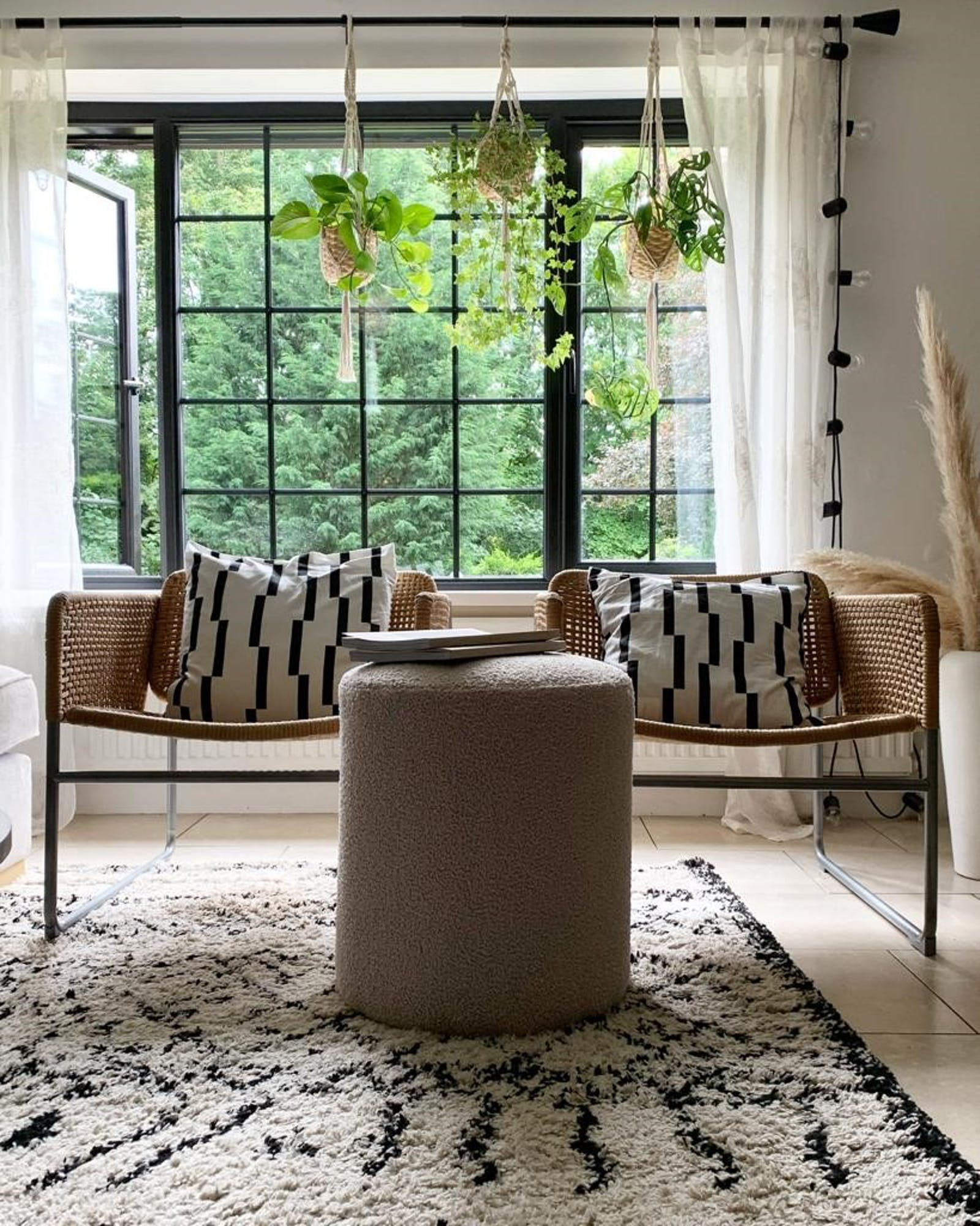 Two chairs in front of big sash windows with black and white patterned cushions