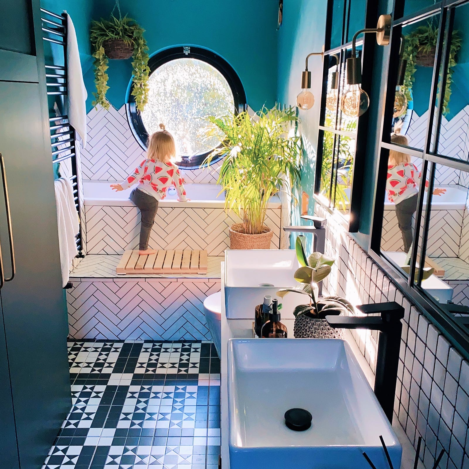 Teal ensuite bathroom with blonde child climbing in bath