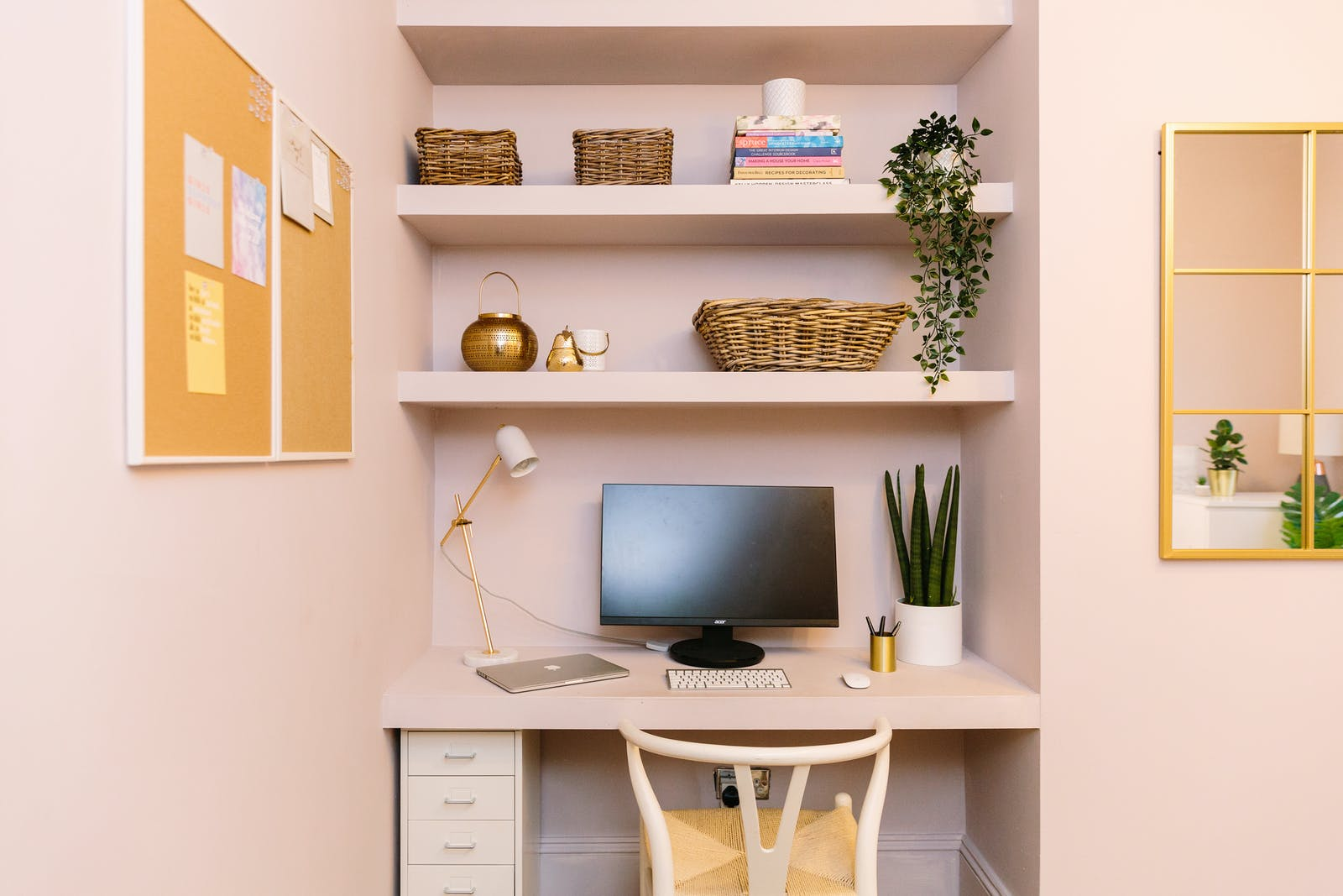 Neat, minimal home office with plants and pink walls