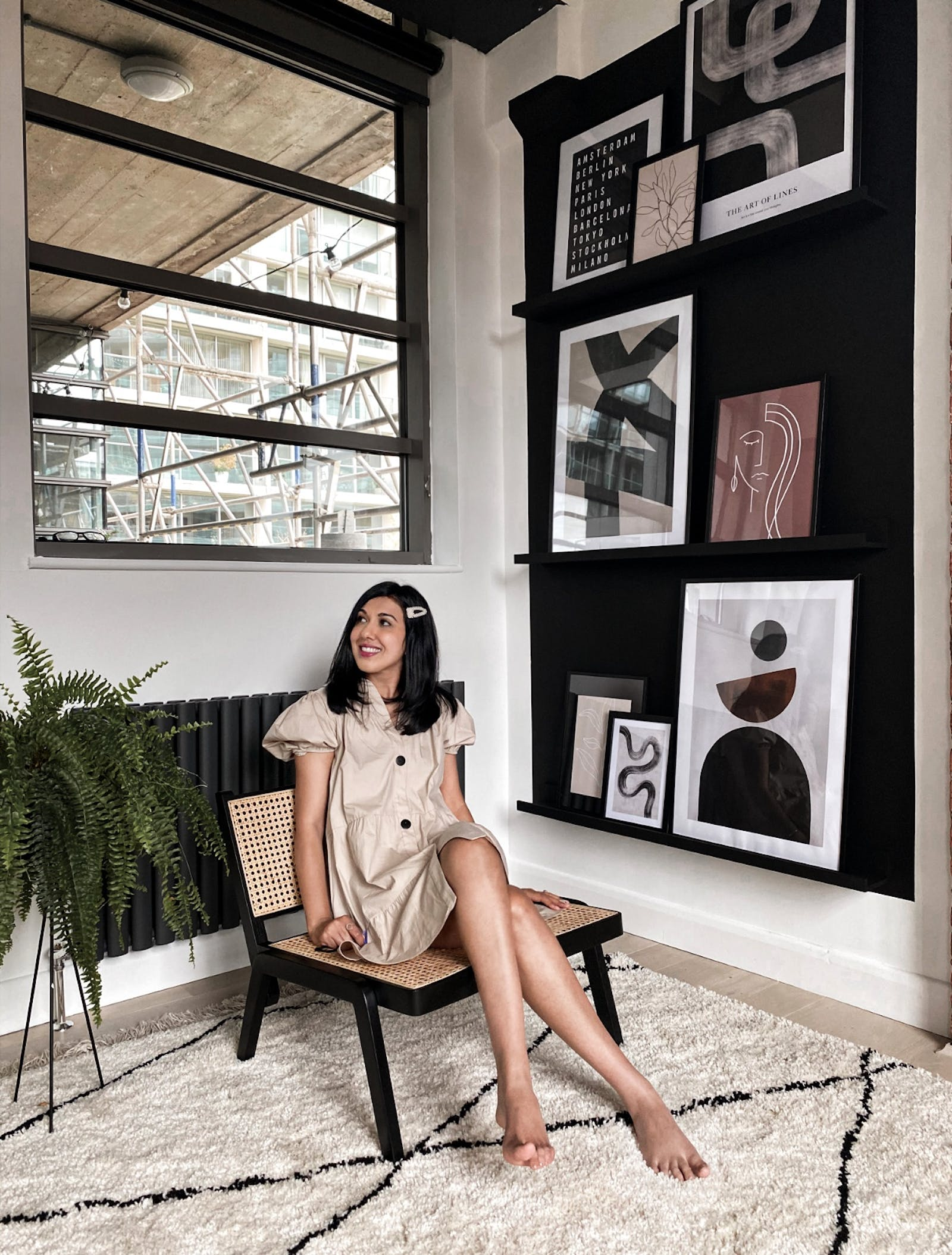 Woman with black hair sitting on a chair in front of a gallery wall