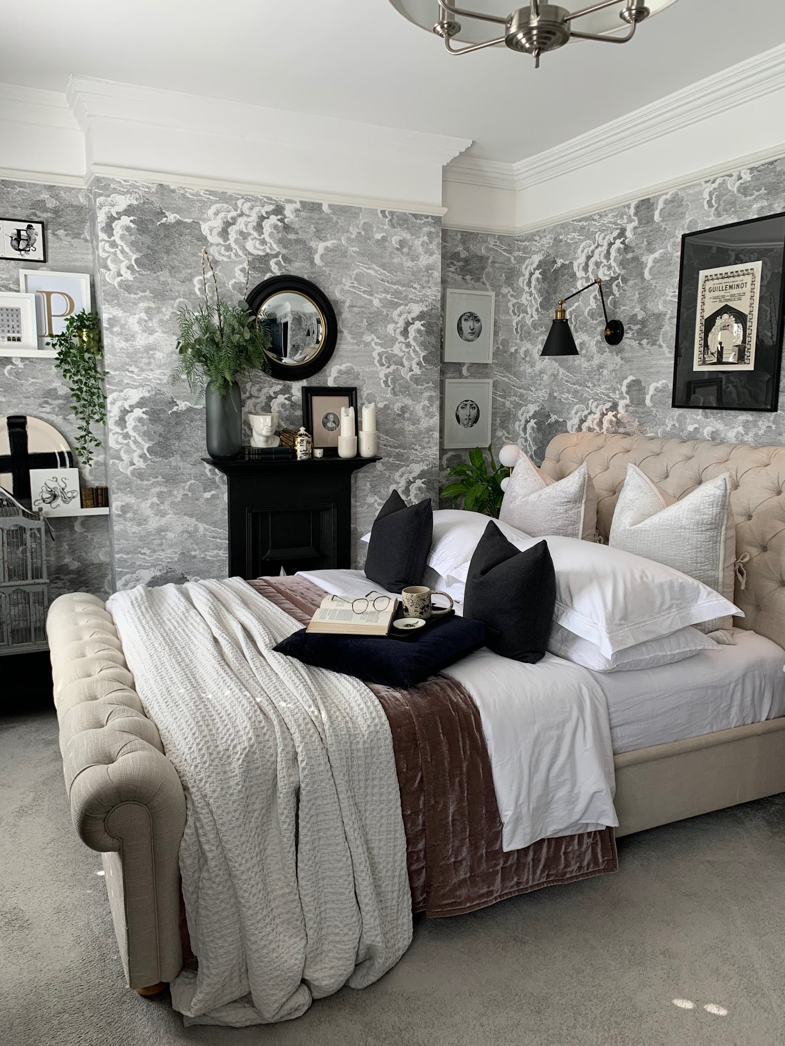 Bedroom with grey wallpaper, picture frames and dark accessories