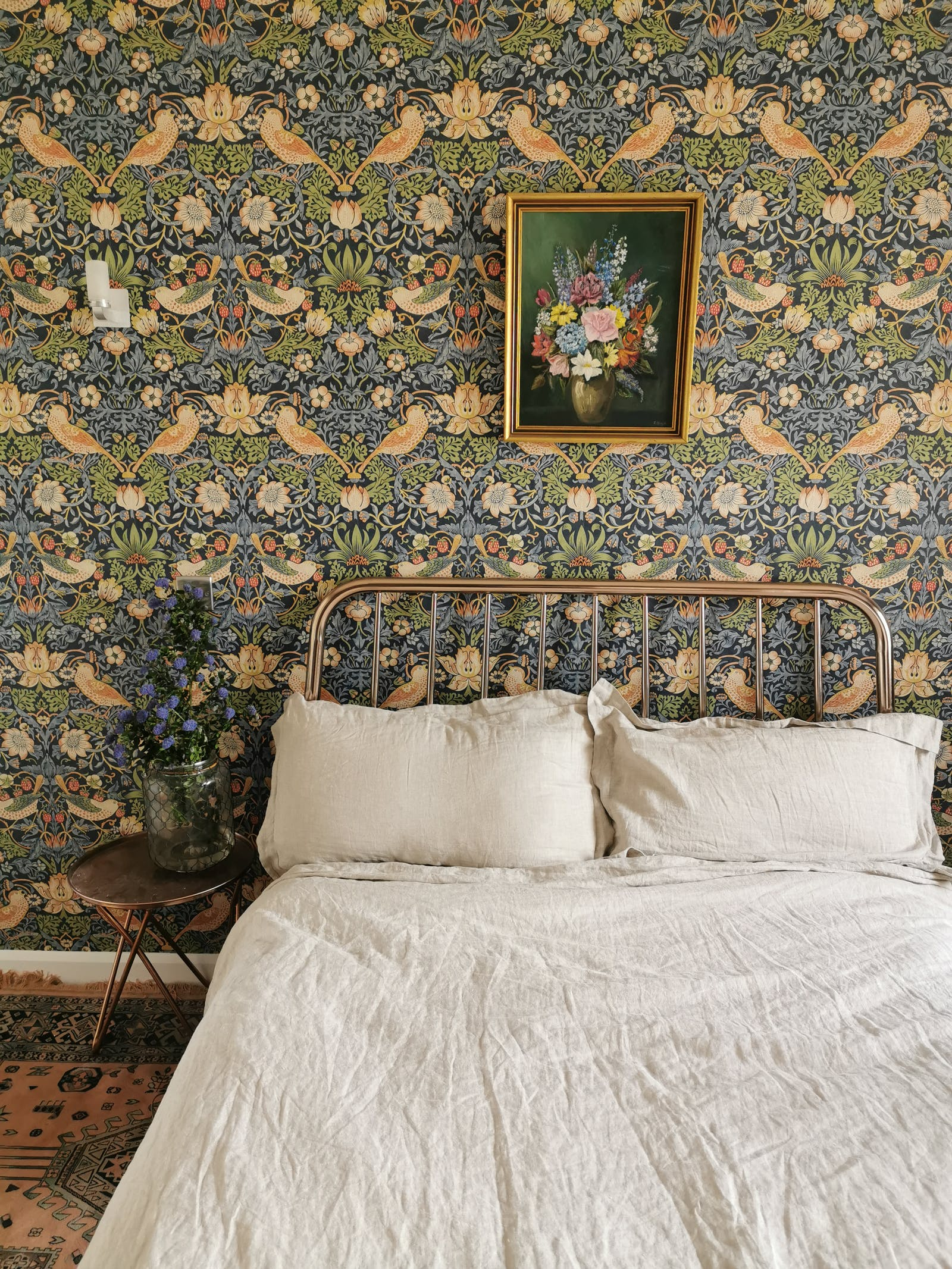 bedroom with patterned floral wallpaper behind it and artwork with flowers