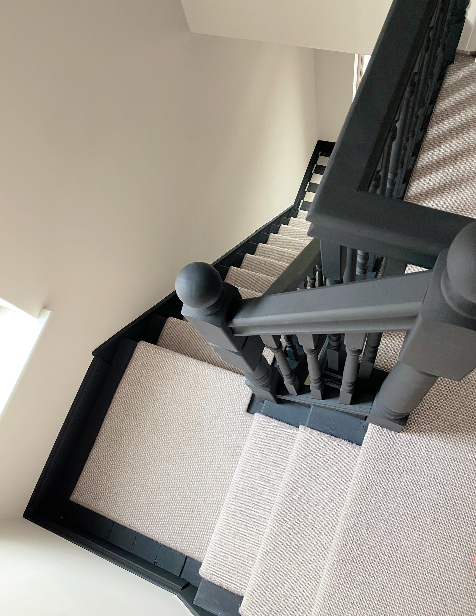 Bird's eye view of stairs with black railing and skirting board