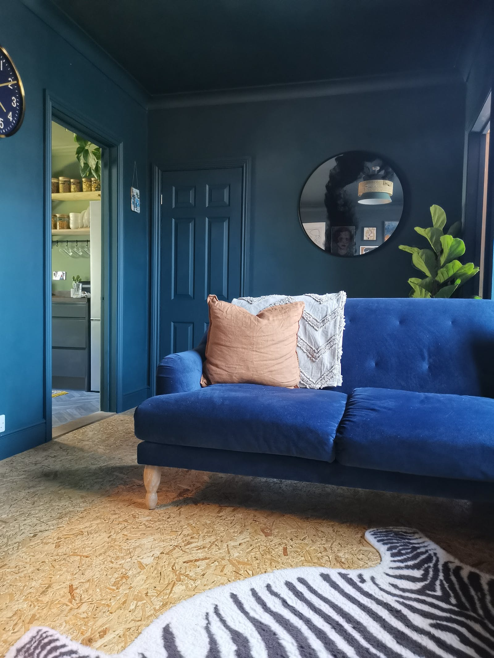 Living room painted in dark blue with a dark blue velvet sofa