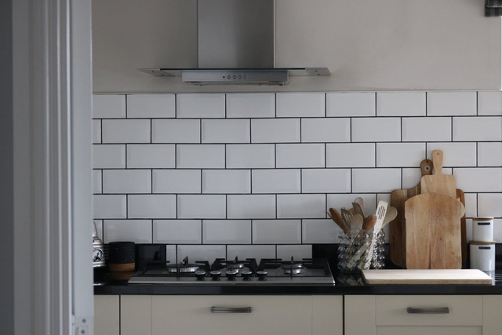 Close up of a kitchen with white tiles on the wall
