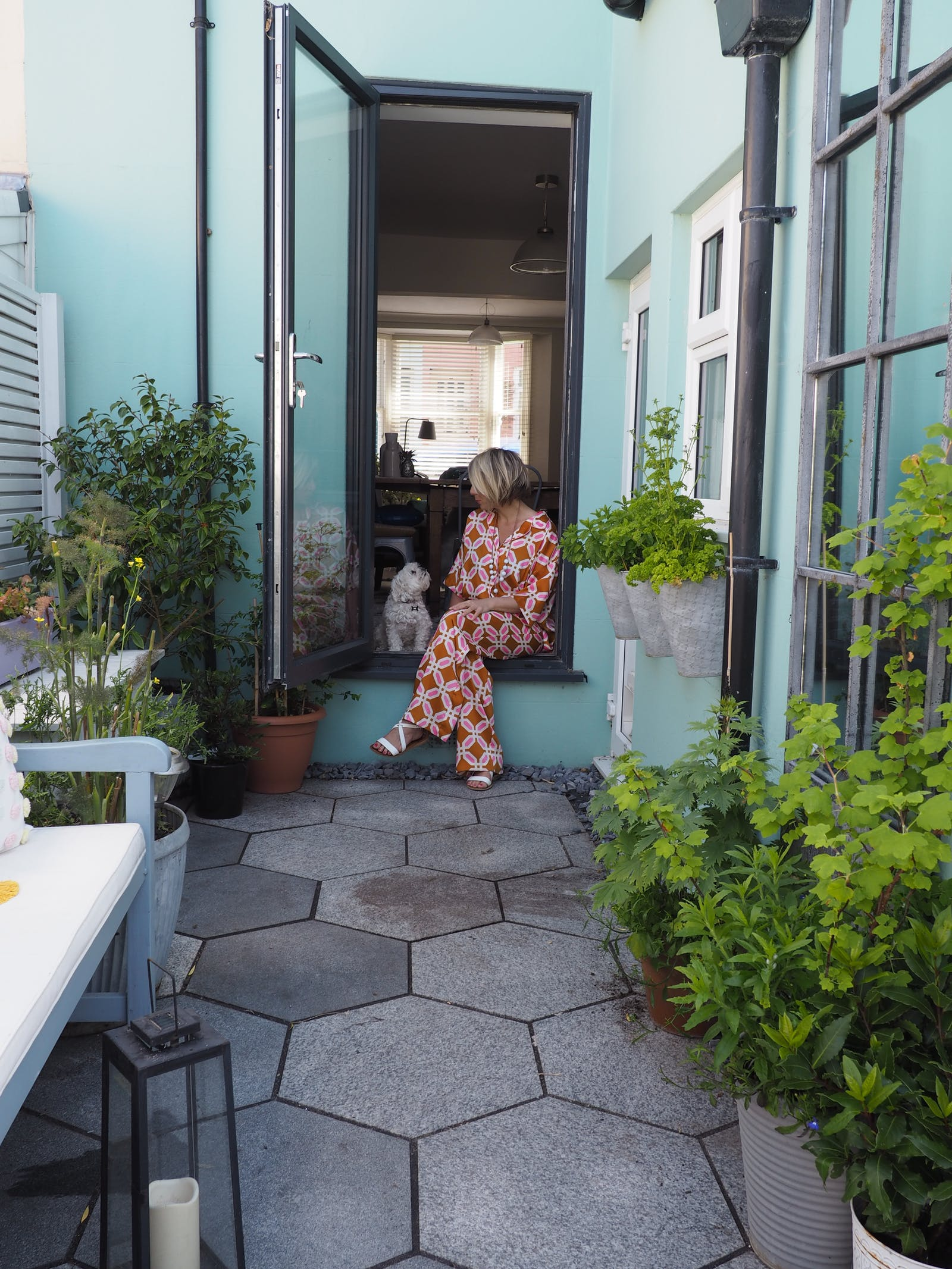Blonde woman sitting on doorstep with dog