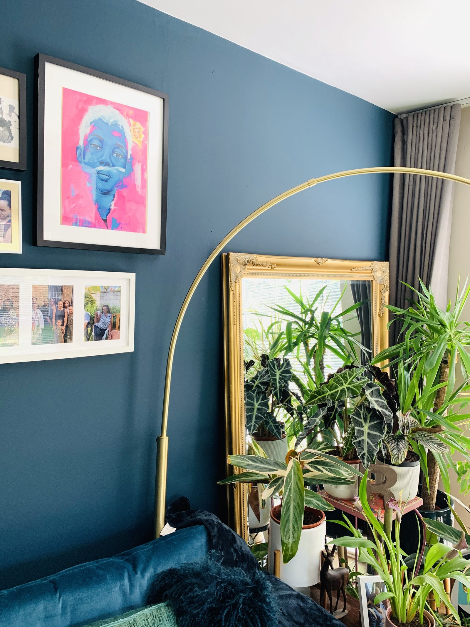 Living room wall painted in Lick Blue 07 with a lot of photos and art frames