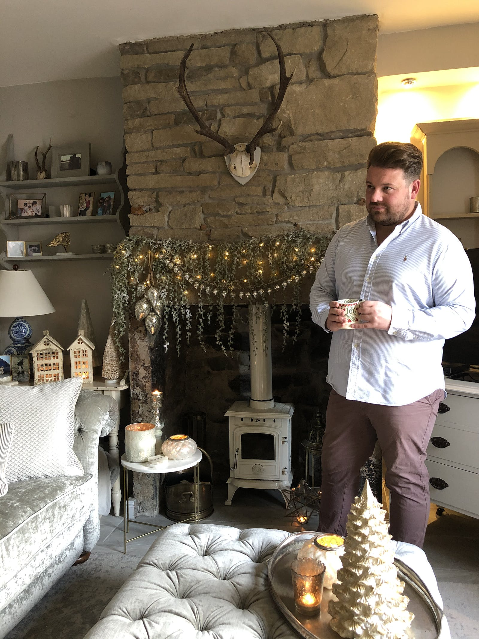 Man standing in front of fireplace decked in Christmas decorations