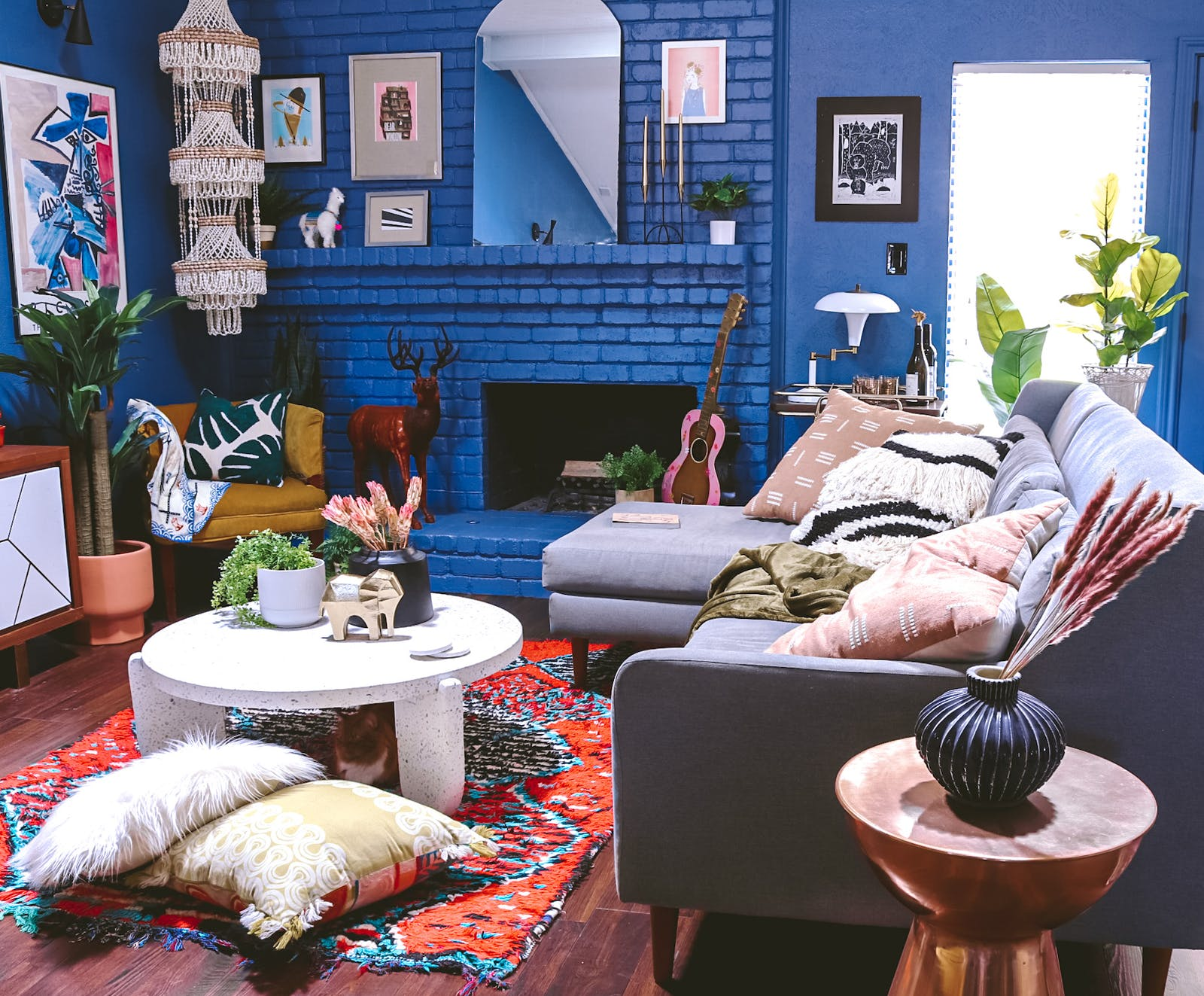 Image of bohemian style living room with deep blue walls and many eclectic ornaments