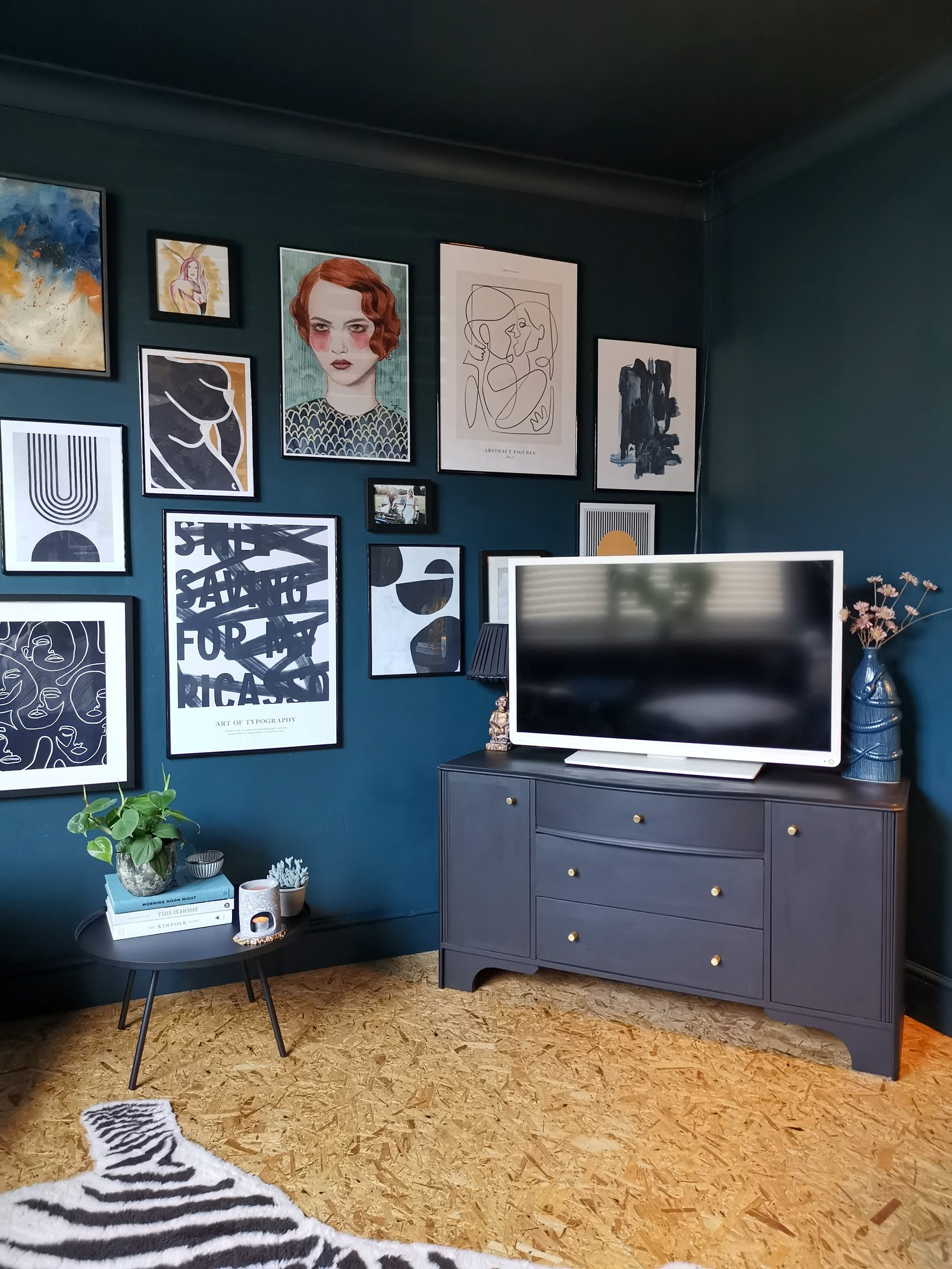 Living room painted in dark blue with a big gallery wall, cork floor and a tv stand with tv
