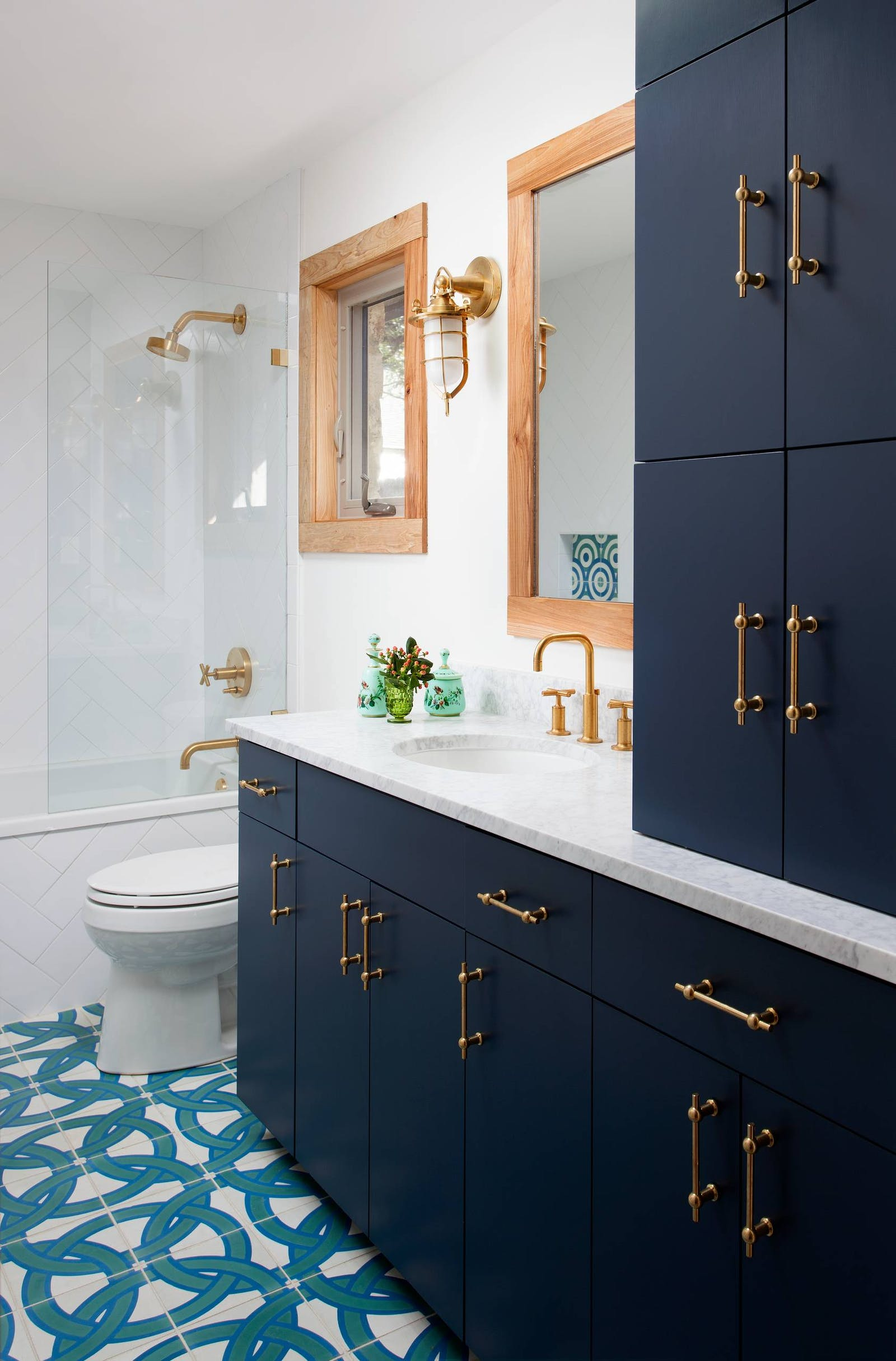 Bright bathroom with tiled floors and navy cabinets