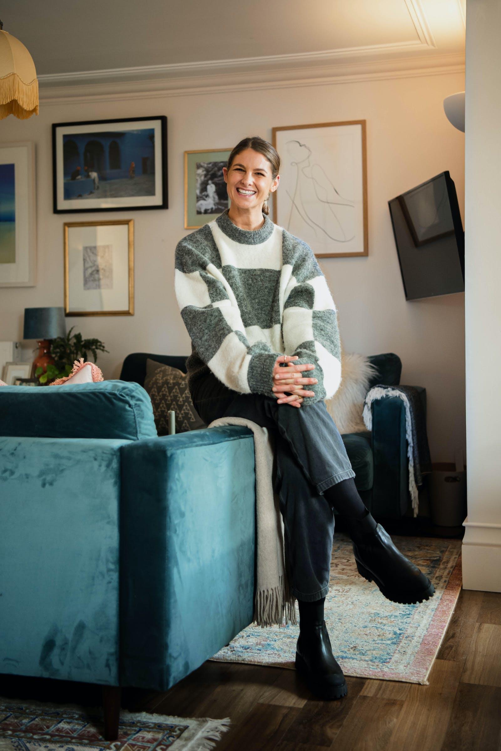Natasha Bradley smiling and sitting on couch