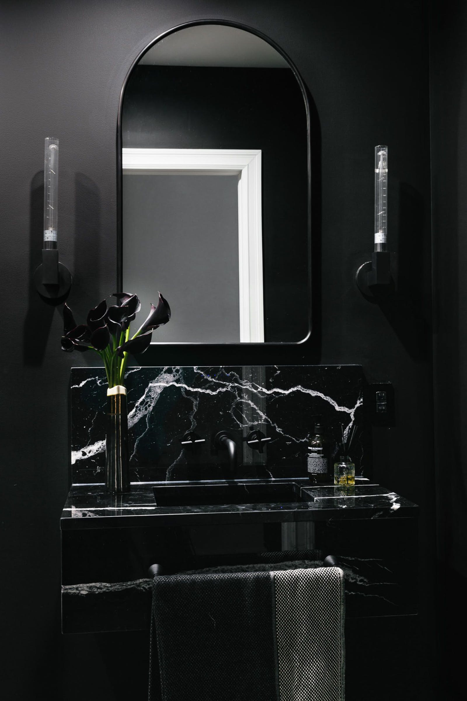 Dark black bathroom with a marble sink and mirror above it