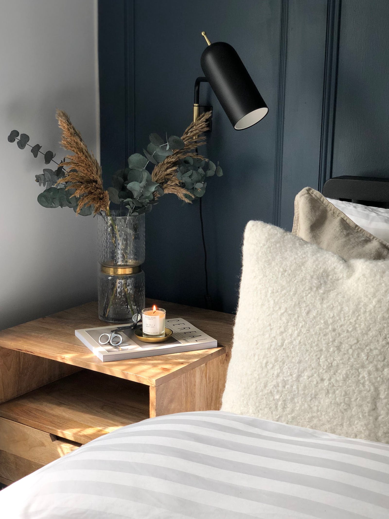 Scandinavian inspired bedroom with dark blue wall panelling, dried flowers and neutral bedding
