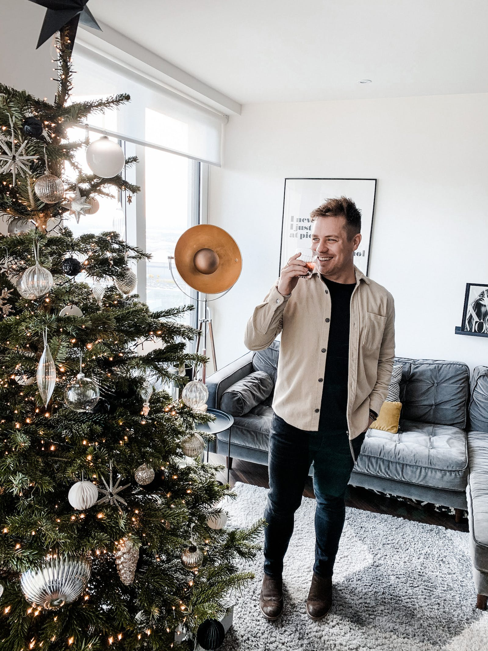 Man standing next to Christmas tree, drinking mulled wine