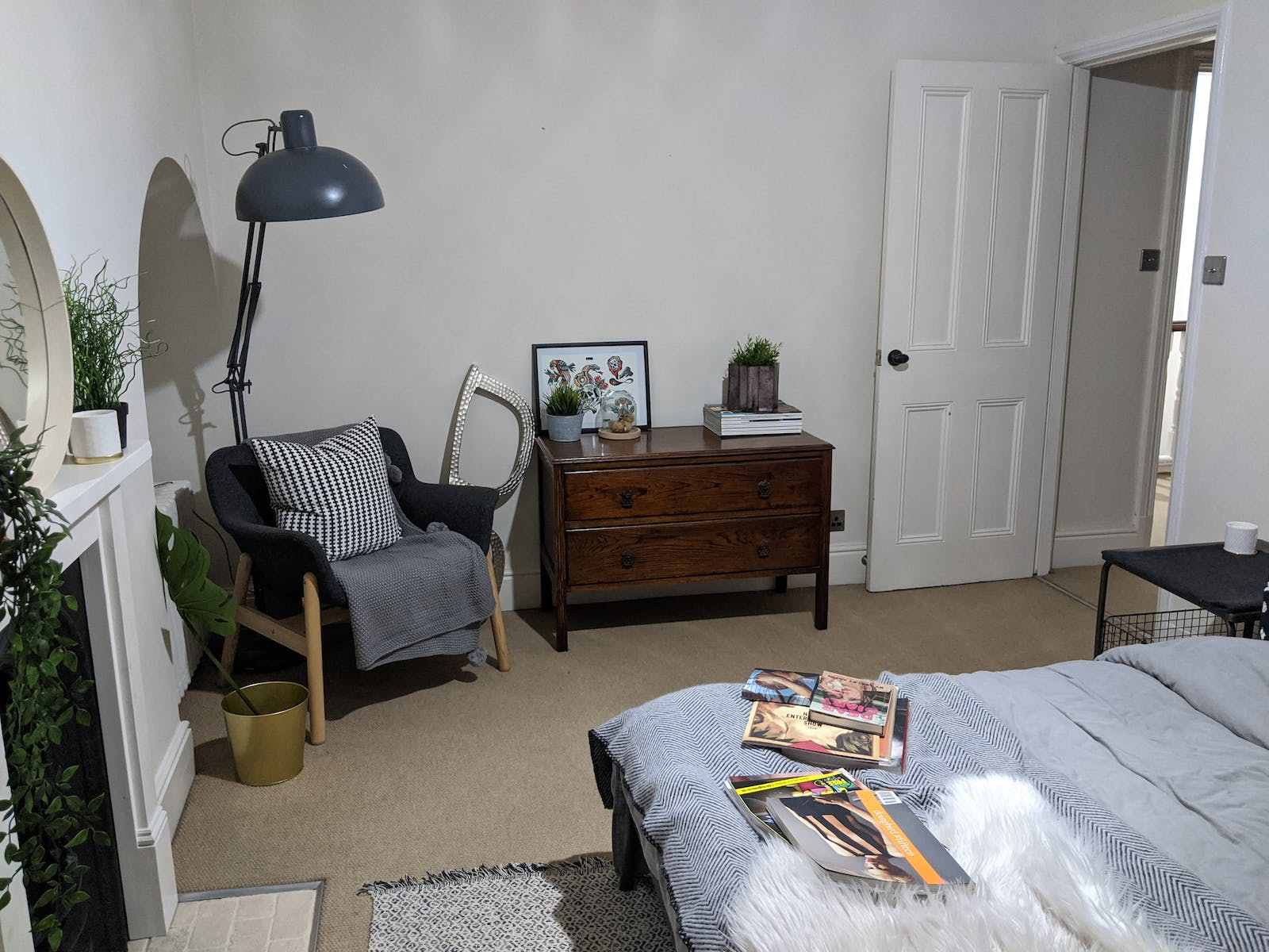 Bedroom in with white walls decorated with cabinet and a grey one-seater