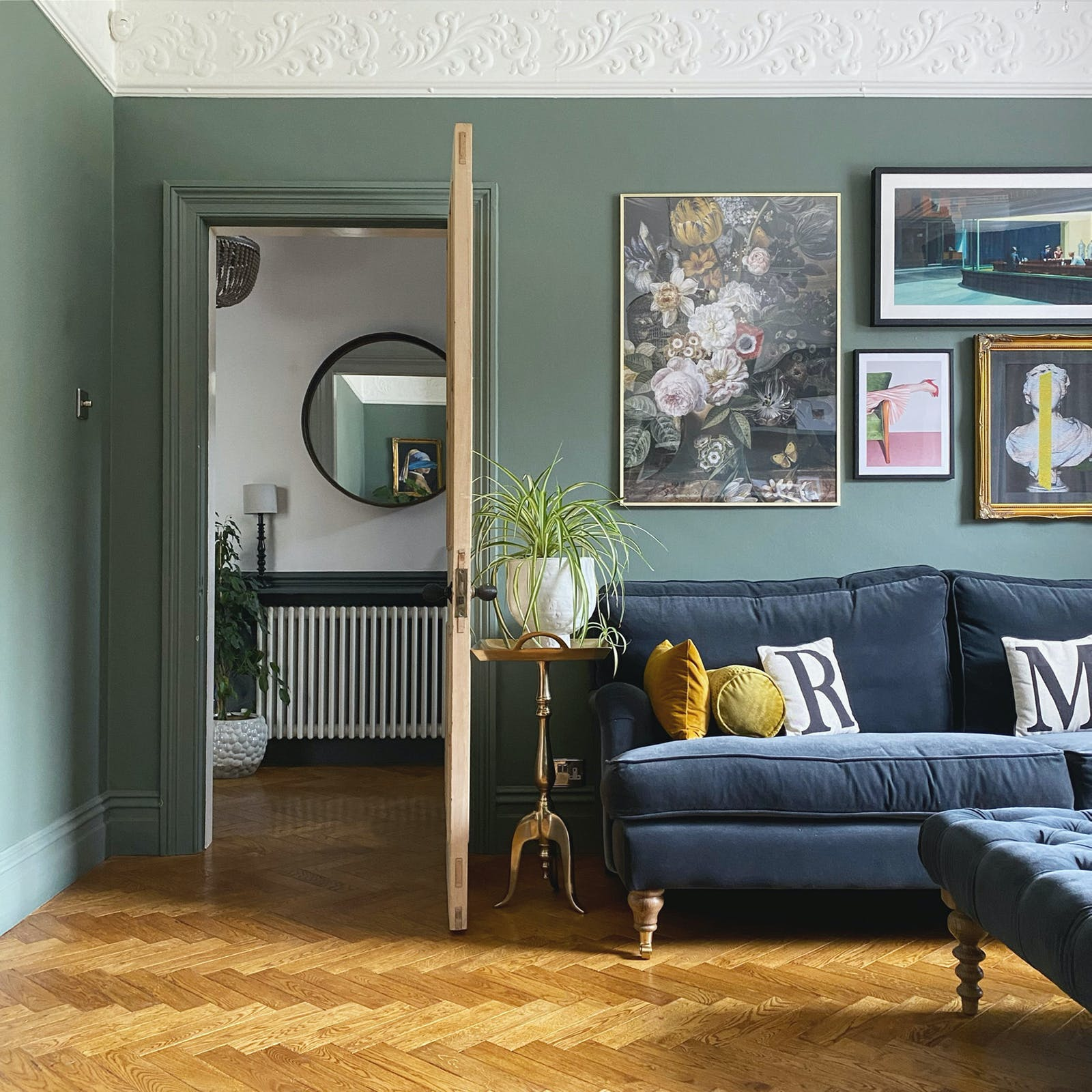 Living room painted in sage green with wooden floor, navy blue sofa and gallery wall