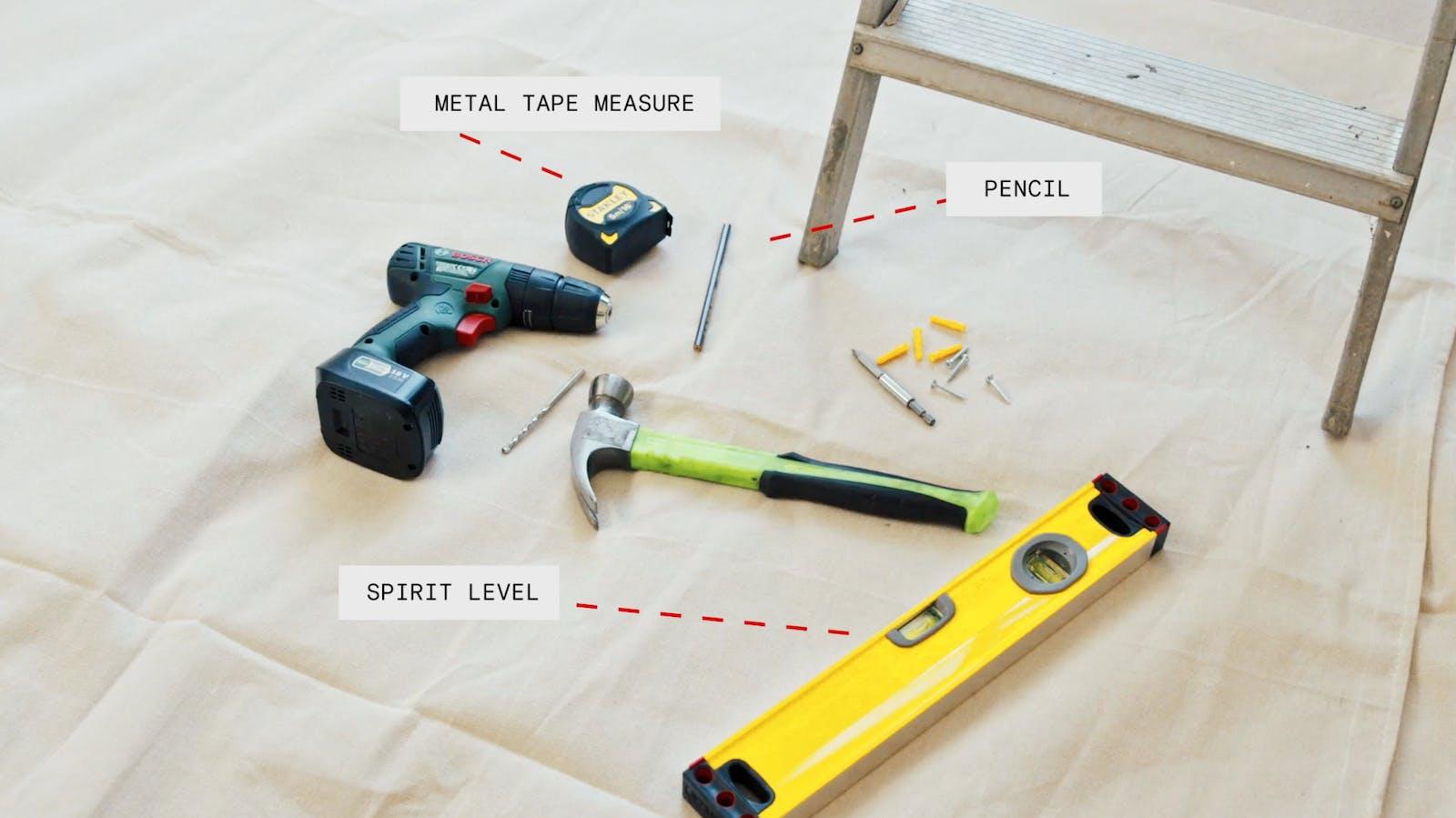 Metal tape measure, pencil and spirit level on floor
