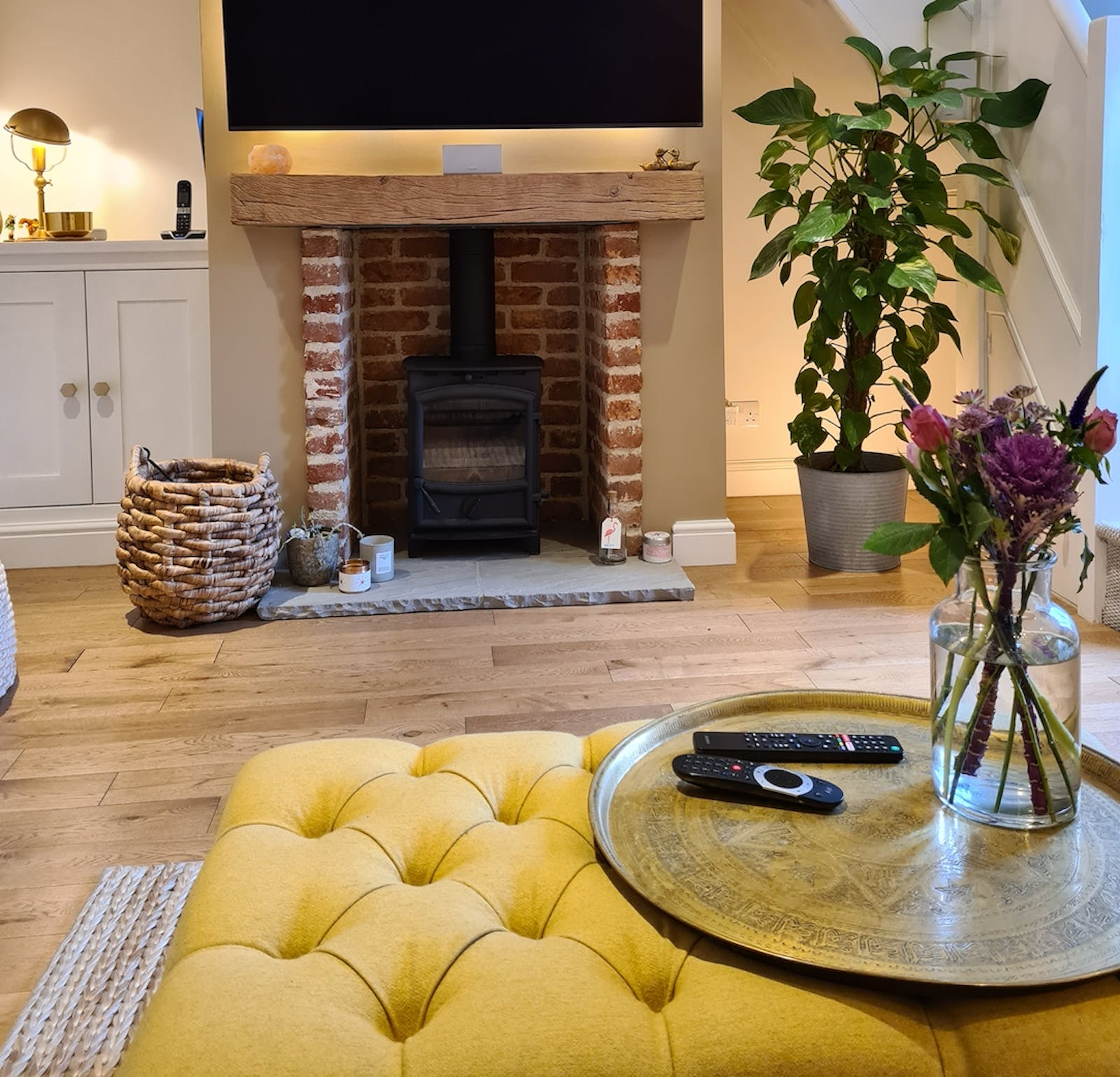 Living room with yellow foot stool, pink flowers and cosy fireplace
