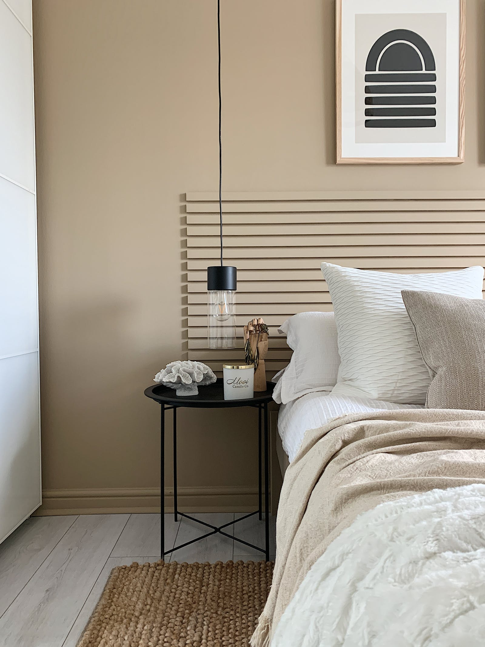 Black bedside table against wall painted in Lick Beige 02