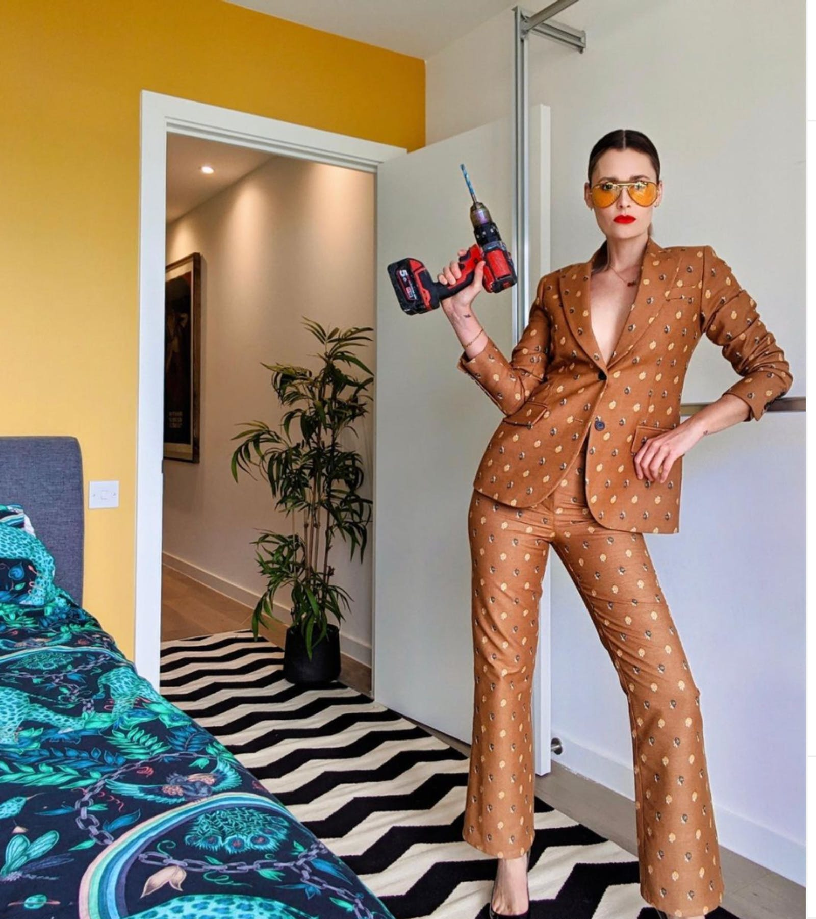 Stylish woman posing with drill in front of Yellow 02 feature wall