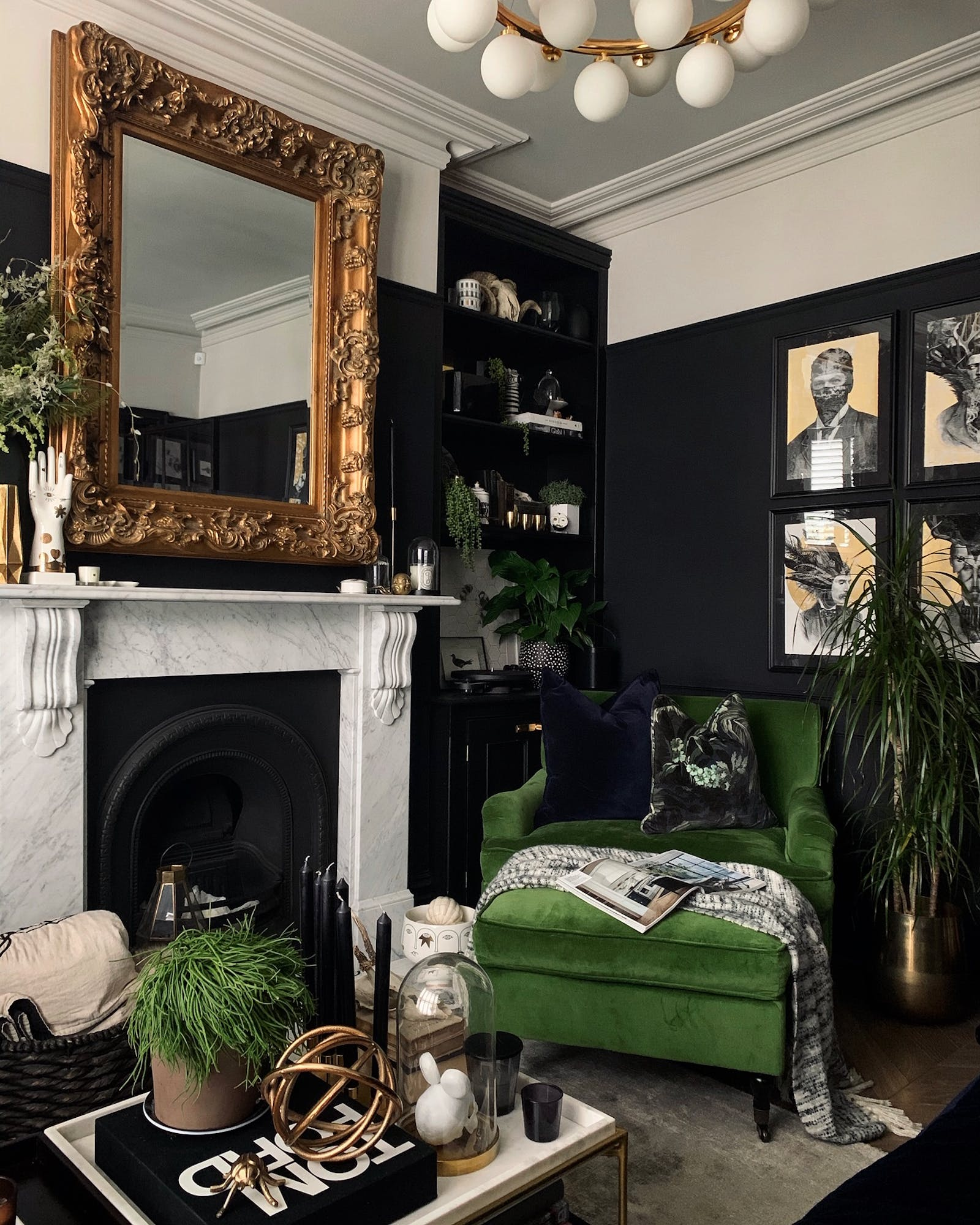 Fireplace, a vintage square mirror and a velvet green armchair arranged in front of a wall painted in black