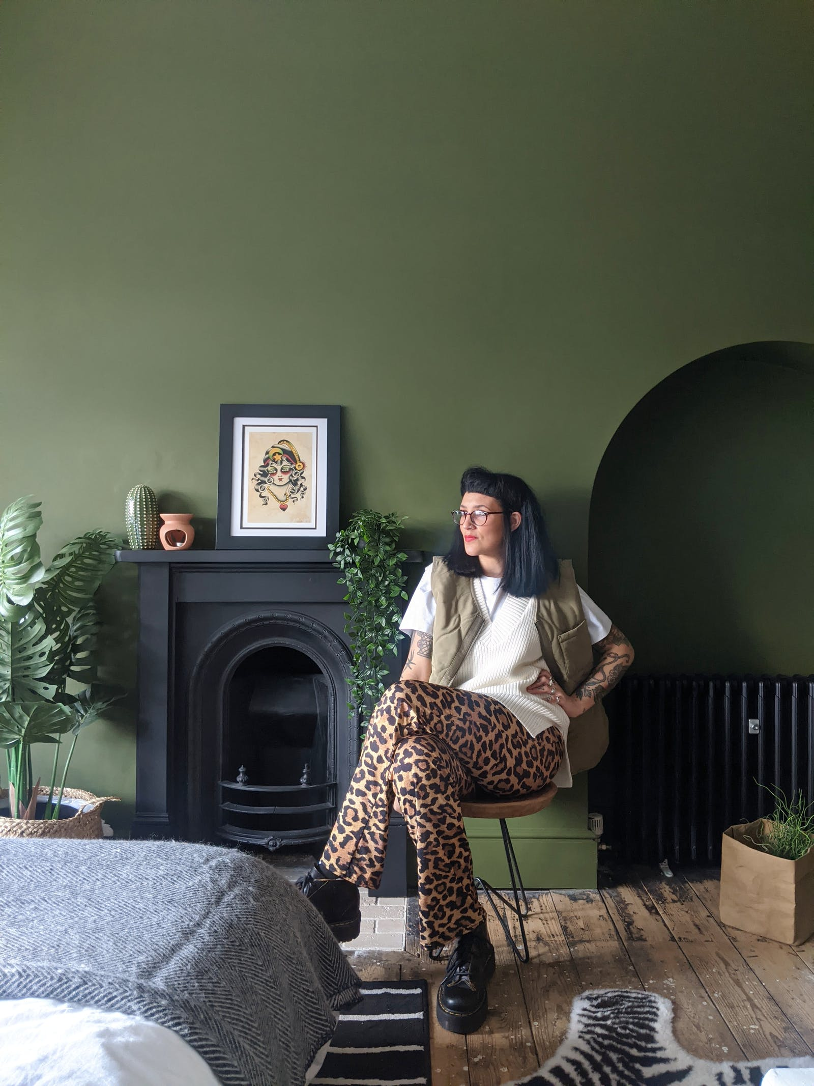 Woman sitting on a chair next to a fireplace and wall painted in Lick Green 05