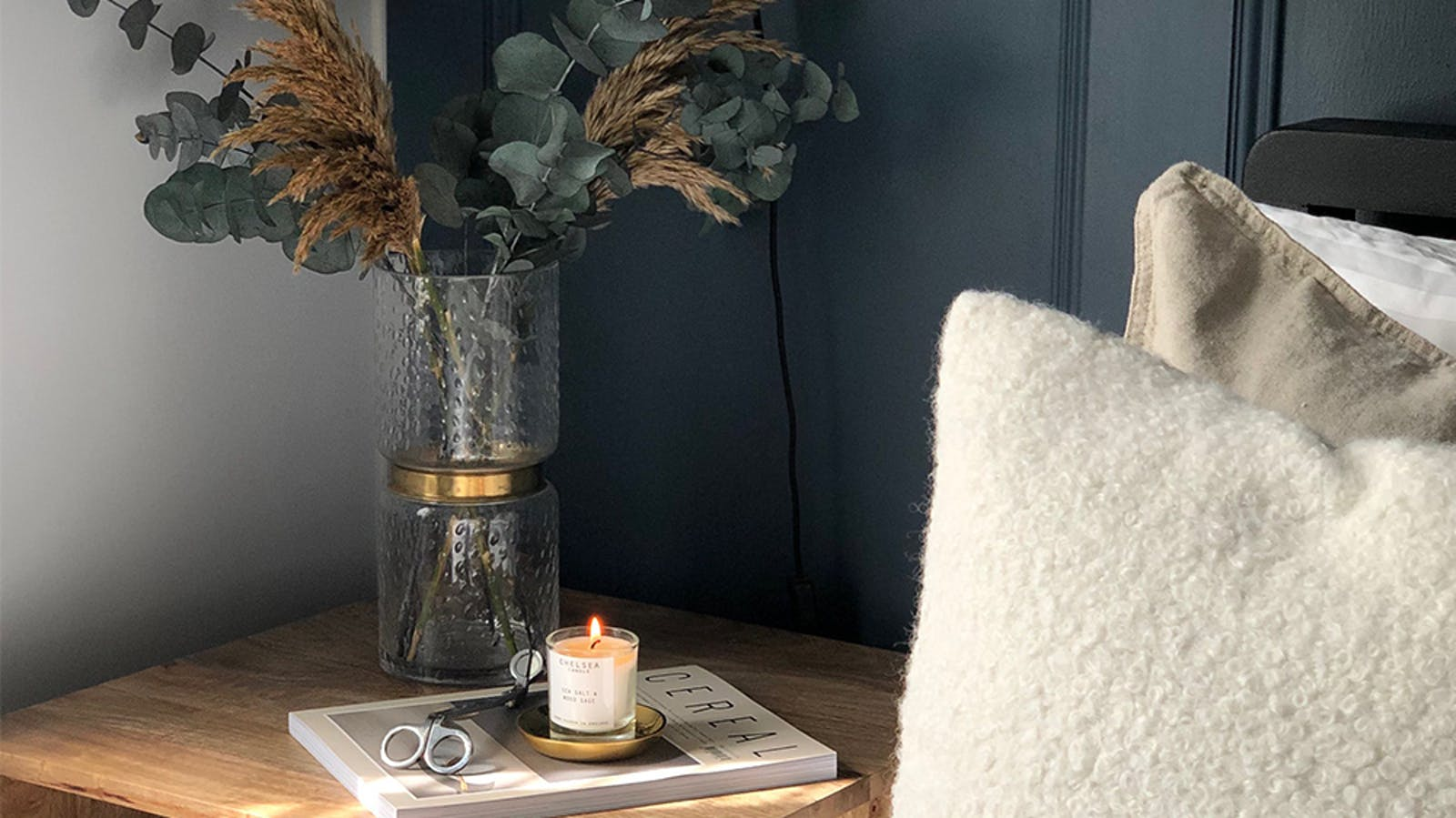 Close up of bed side table with a lit candle, a magazine and some dried eucalyptus flowers