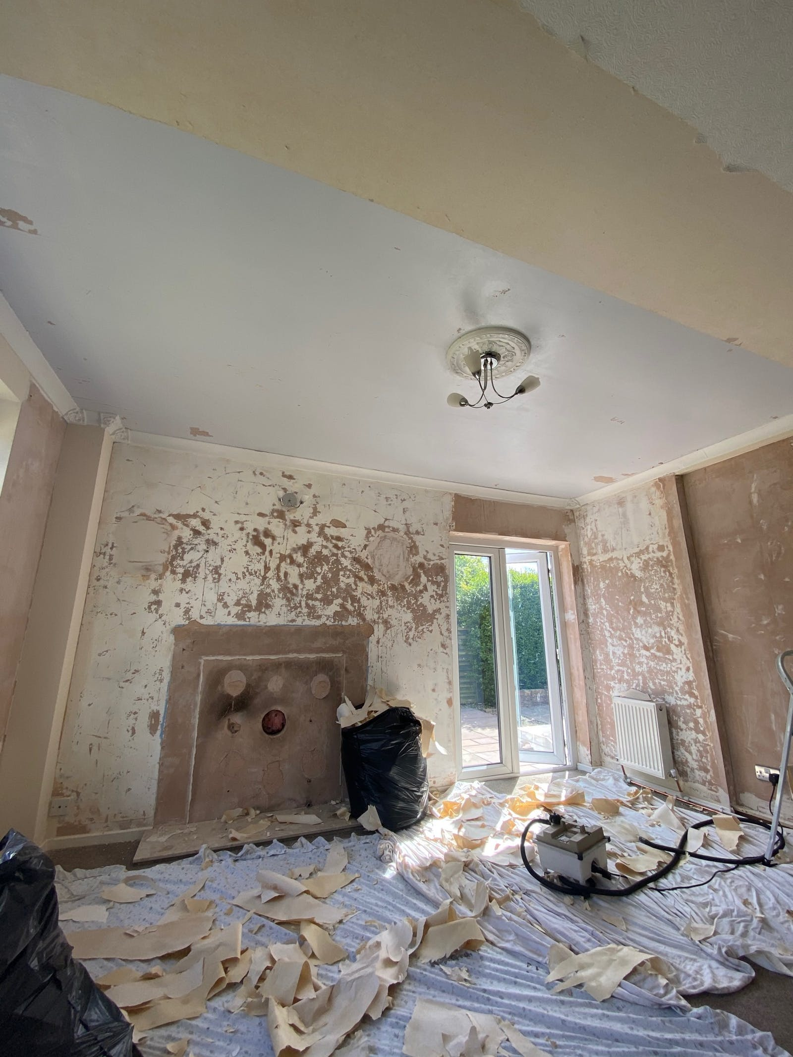 DOAB Before picture of room with peeling plaster and decorating equipment