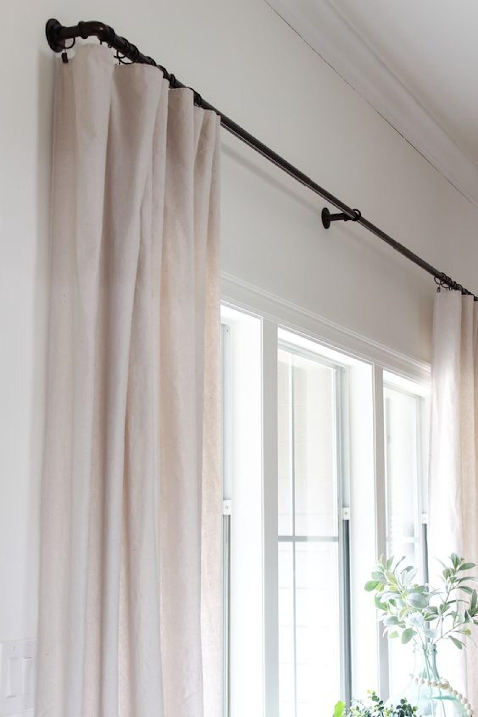 Black curtain rail with white linen curtains