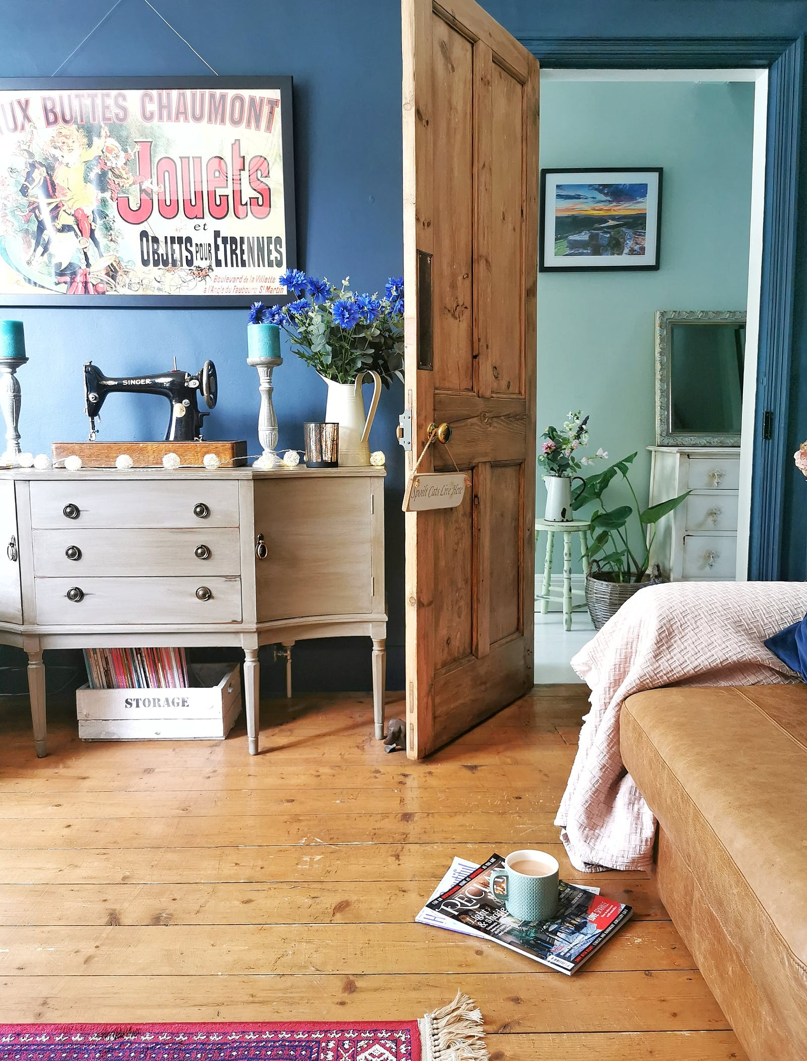 Living room painted in dark blue with vintage furniture, wooden details and vintage poster on the wall
