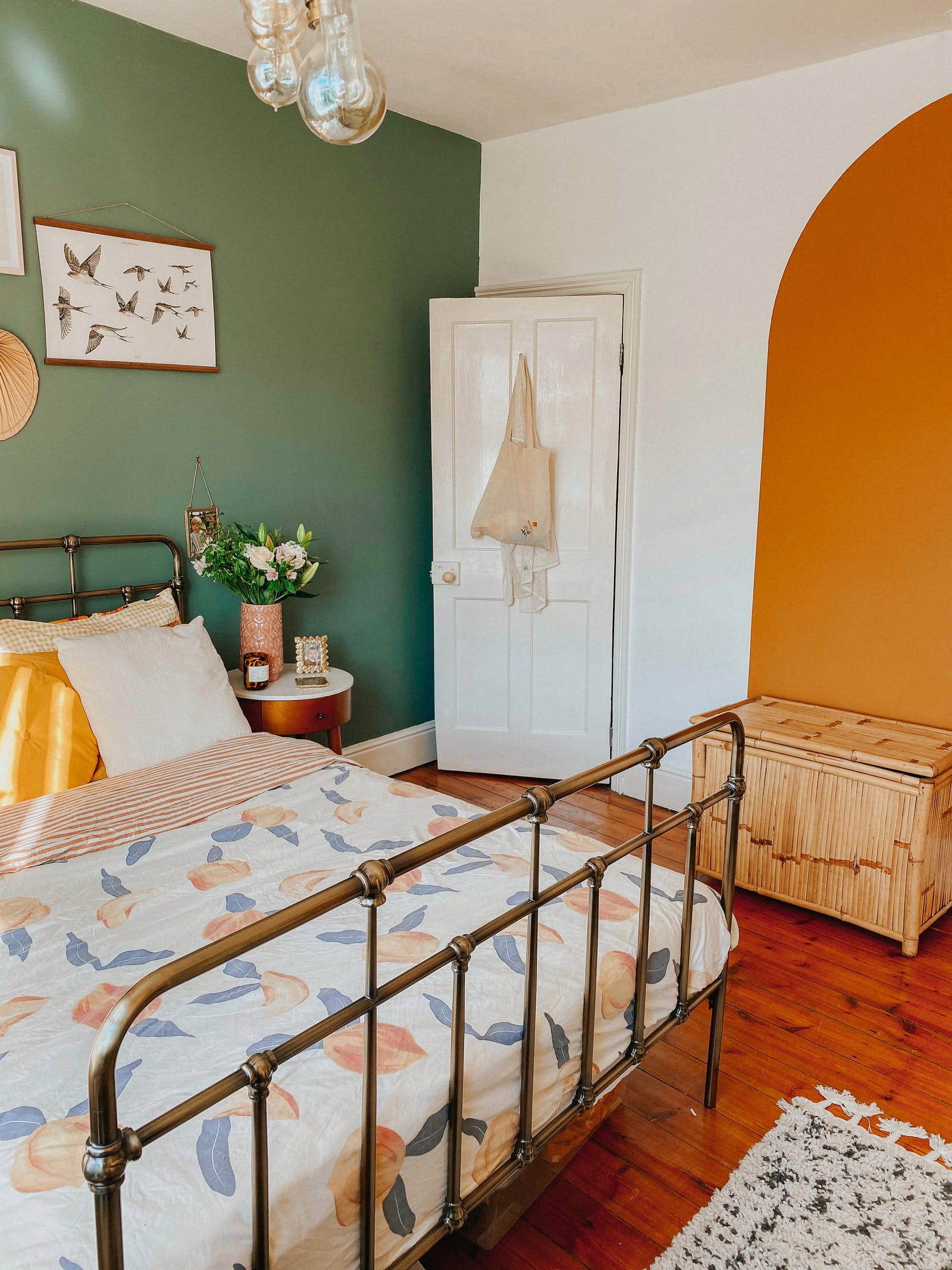 A bedroom with a green feature wall and an orange painted arch using Lick Orange 02