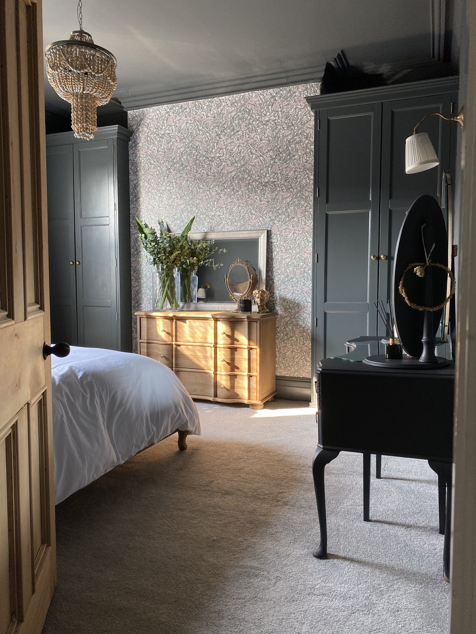 Bedroom with graphic wallpaper and dark grey wardrobes