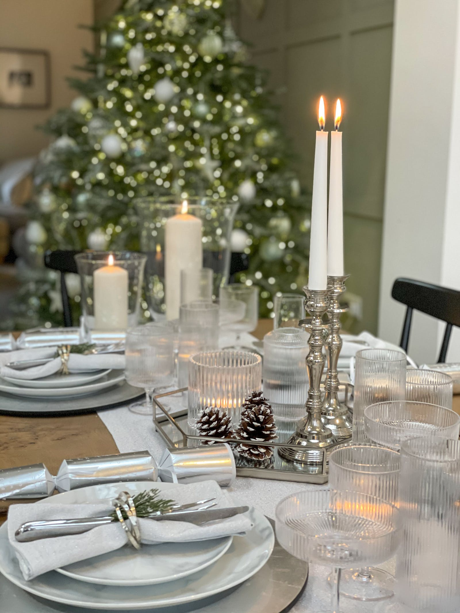 Dining table with Christmas decorations and burning candles on candle sticks