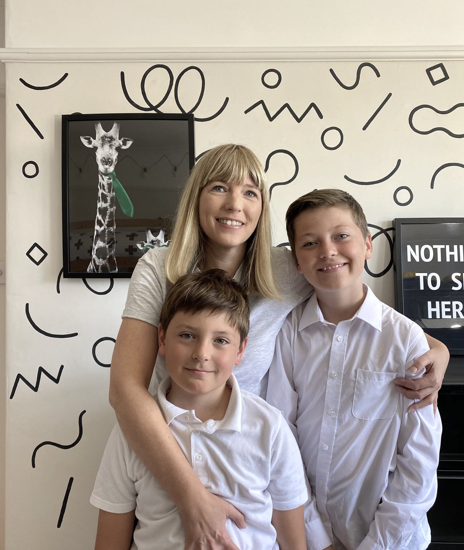 Blonde woman with two kids in front of a geometric pattern wall
