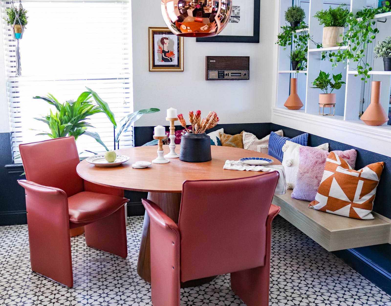 Image of retro dining room area with terracotta chairs, a fish bowl hanging light and various plants