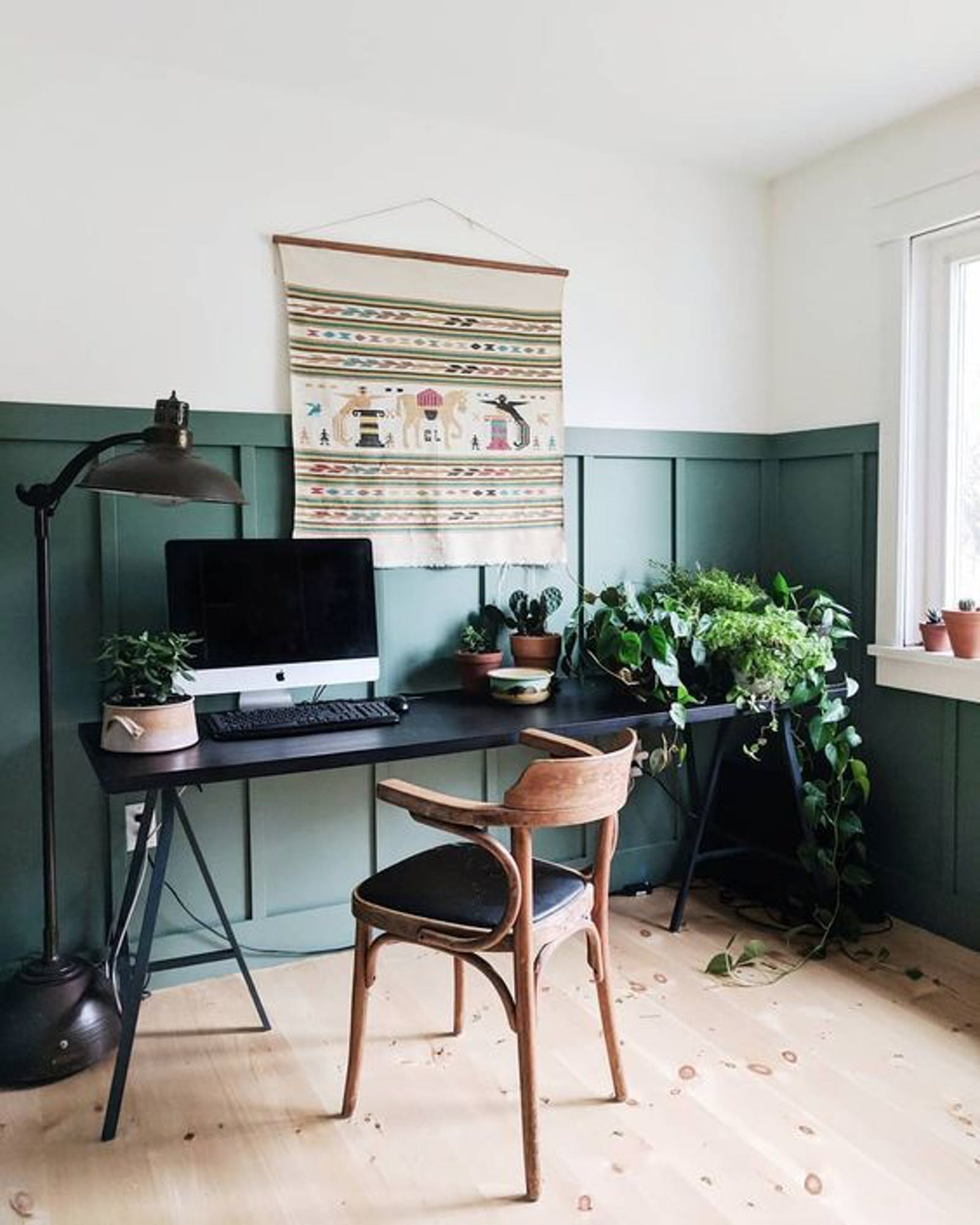Home office area with a two-tone wall painted in white and green, wooden chair and green plants