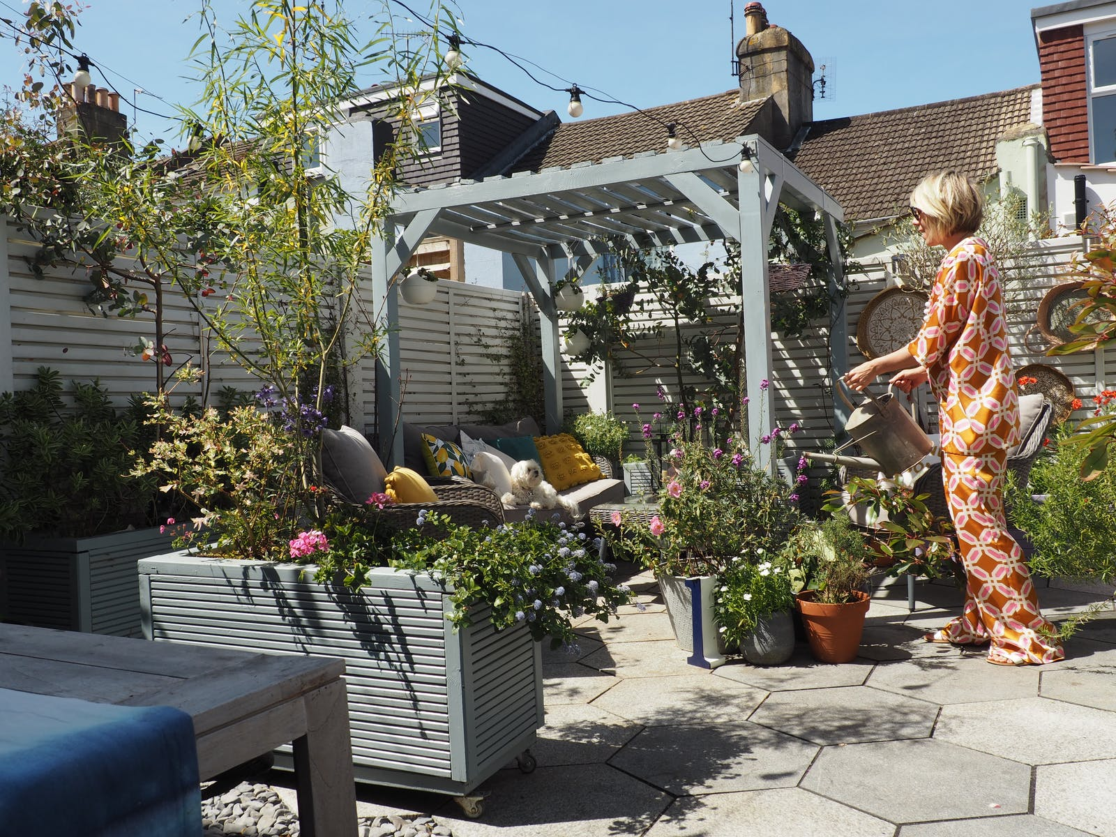 Blonde woman with pixie cut standing in garden watering a plant