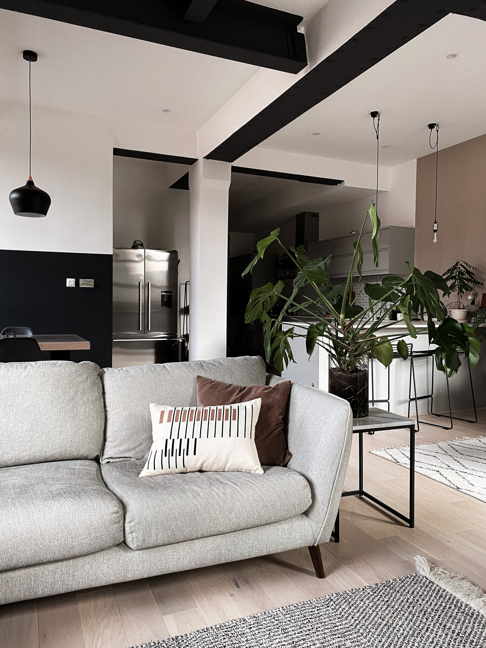 Living room with a grey sofa and kitchen in the background