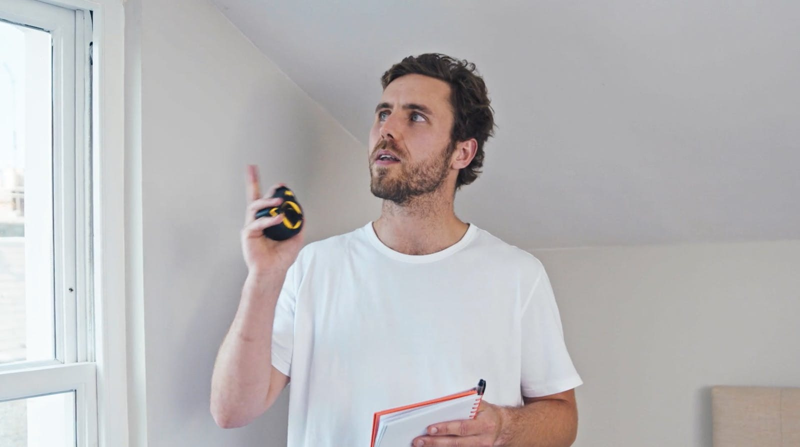 Man holding metal tape measure pointing to a window