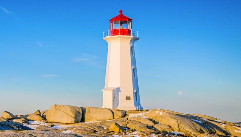Peggy's Cove Lighthouse under blue summer sky. Peggy's Cove, Nova Scotia, Canada.