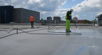 Jet washing single ply roof covering on flat roof prior to installation of Liquasil DG flat roof waterproofing